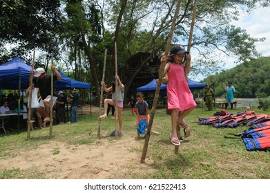 """Kiulu Sabah Malaysia - Apr 15, 2017 : Tourist trying out traditional game locally known as """"Rampanau"""" a walking with bamboo poles. Traditional game is among activities in eco tourism in Sabah Borneo."""