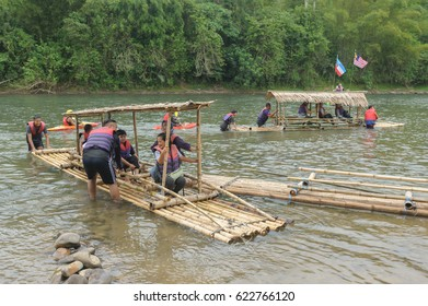 Kiulu Sabah Malaysia - Apr 15, 2017 : Tourist trying out traditional bamboo raft at Sondoton Kiulu. Experiencing native people daily life activities is a part of ecotourism attraction in Sabah Borneo.