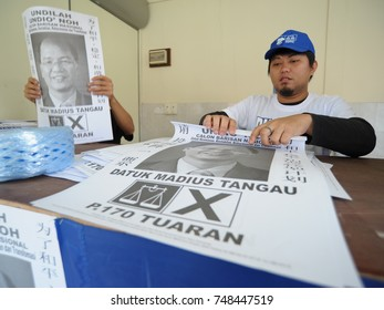 Kiulu Sabah Malaysia - Apr 21, 2013 : Barisan Nasional (BN) party worker preparing campaign banner during 13th Malaysian General Election in Kiulu. BN is the biggest political party in Malaysia.
