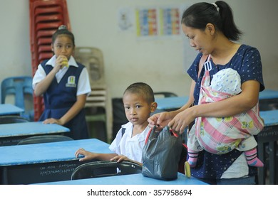 Kiulu Sabah Malaysia - Jan 4, 2016:Unidentified mother accompanying his kids to attend first day school session of 2016 on Jan 4, 2016 at gorvenment school in Kiulu Sabah Malaysia.