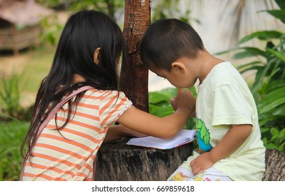 KIULU, SABAH MALAYSIA- JUNE 05, 2017: A little girl helping her cousin with drawing on an old tree stump at the park