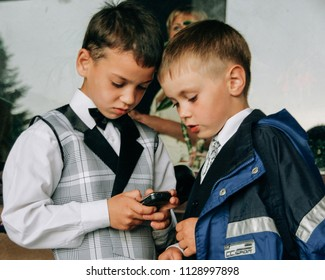 Kiverci, Volyn / Ukraine - June 27 2009: Two boys playing with cellphone on street