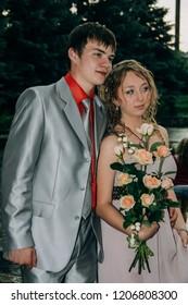 KIVERCI, Volyn / UKRAINE - June 27 2009: Loving teenage couple with flower bouquet posing in park