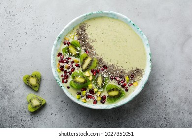Kiwi banana smoothies bowl with oatmeal, pistachio nuts, pomegranate seeds and chia on light gray stone background. Selective focus. Top view. Copy space.