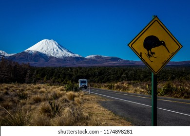 Kiwi bird crossing sign on road to Mount Ruapehu with camper driving past