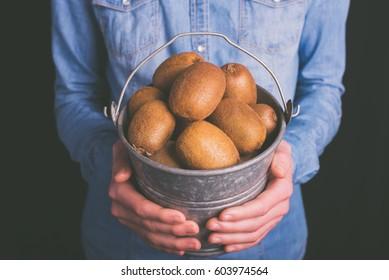 kiwi bucket in hands - vegetarian and vegan people - vintage style filter
