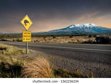 Kiwi crossing sign at night next to snowy Mount Ruapehu in New Zealand's Tongariro national park.