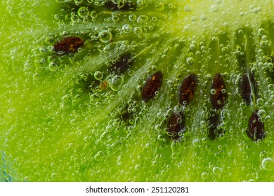 Kiwi fruit in water with bubbles over green background.