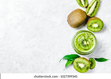 Kiwi fruits and green smoothie in glass jar on white background. Top view, space for text.