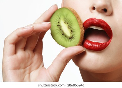 Kiwi in hand, female lips painted bright red lipstick