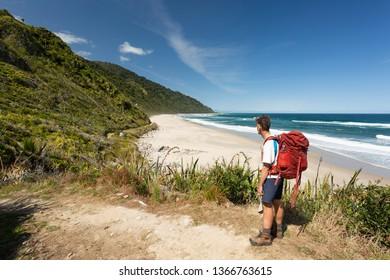 Kiwi hiker tramping beach section of Heaphy Track, Kahurangi National Park, New Zealand