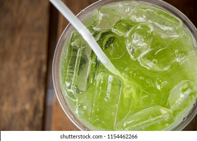 Kiwi Italian Soda with Ice in glass placed on wooden table
