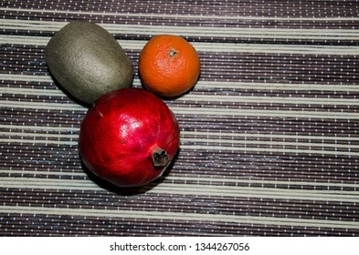Kiwi, mandarin and pomegranate on stripped bamboo sheet, healthy fruits