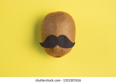 Kiwi with a mustache on a bright yellow pastel background