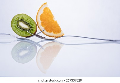 Kiwi and orange fruit slices composition on two intertwined forks