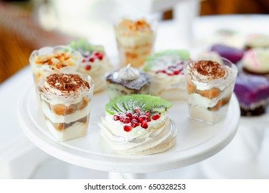 Kiwi and pomegranate biscuit cake and other desserts in the background on a wooden white dessert stand at a party