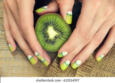 Kiwi and skin care of a beauty female hands with green and white moon nail art manicure on a sackcloth and wooden background