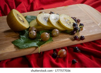 Kiwi sliced, gooseberries and black currants with leaves on a wooden board on a  red background