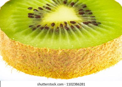 Kiwifruit slice placed on a white background with the seeds in focus.