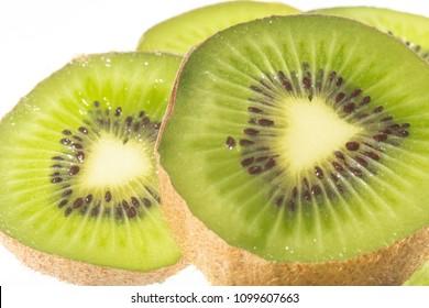 Kiwifruit slices placed on a white background.