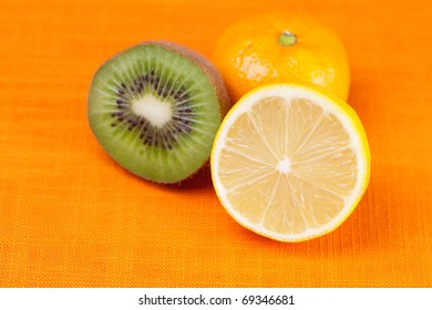 kiwi,lemon,mandarin  lying on the orange fabric
