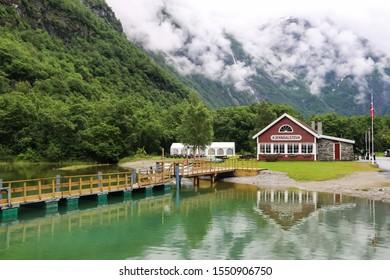 Kjenndal Valley/Norway - July 15, 2015: Beautiful Norwegian restaurant (Kjenndalstova) in the middle of Kjenndal Valley during a raining day. Mirror lake and foggy mountains.