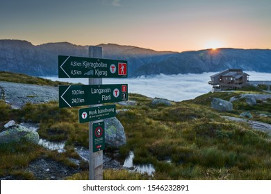 Kjerag, Norway -  July 12, 2019: signpost began climbing a Kjerag mountain in southern norway in the background dawn and a hotel building on the edge of a cliff