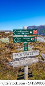 Kjerag/Norway - 5 19 2018: A sign leading to Kjerag and Langavatn, Norway. Sign is located in a hiking trail, marking the right way for the hikers. In the back massive mountain range. Bright and sunny