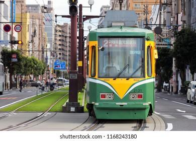 KKAGOSHIMA, JAPAN - APRIL 10, 2010: Tram on route 2 between Kagoshima-Ekimae, Takamibaba, Kagoshima-Chuo-Ekimae and Korimoto arriving at Kagoshima Chuo-Ekimae (Kagoshima Central Station) tram stop.