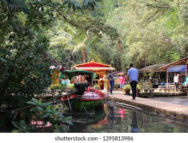 Klaeng, Rayong, Thailand - January 6th, 2019: A tourist from a boat trip walks along a pier in the tropical mangrove forest at Tung Prong Thong, a protected nature reserve in eastern Thailand.