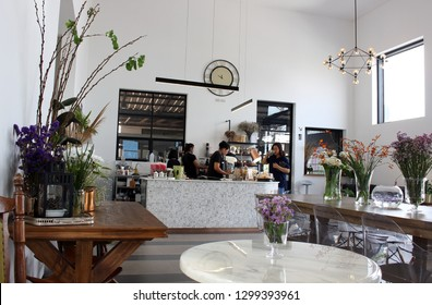 Klaeng, Thailand - January 6th, 2019: View of customers and serving staff in CHIM Kitch Cafe, a trendy coffee shop with modern clean design popular with locals in Klaeng, eastern Thailand.
