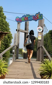 """Klaeng, Thailand - January 6th, 2019: A lady tourist walks through the entrance to Tung Prong Thong Nature Reserve, a protected mangrove forest. The Thai sign reads """"Welcome, nice to meet you."""""""