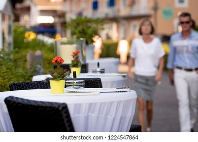 KLAGENFURF, CARINTHIA, AUSTRIA - AUGUST 07, 2018: Cafe tables on the street. In the background is a street with human silhouettes.