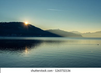 KLAGENFURT/ AUSTRIA DEC 25 2017 - Amazing Winter Sunset on a mountain lake with a view to mountains in Klagenfurt, lake Woerthersee, Austria