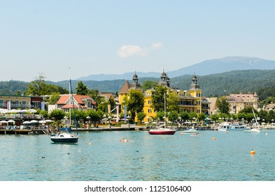 Klagenfurt, Carinthia - Austria - 19.07.2018 : Worthersee view at turquoise water of lake in summer mountains in distance and one of the hotels and resorts. Tourists enjoying summer vacations.