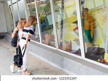 Klaipeda, Lithuania - 26 June 2018: Cute ladies are looking at the cloth shop window. Klaipeda, Lithuania.