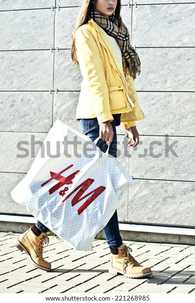KLAIPEDA,LITHUANIA-SEPT 30: Happy young woman with HM bag on September 30,2014 in Klaipeda,Lithuania.H&M Hennes & Mauritz AB (H&M) is a Swedish multinational retail-clothing company.