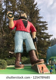 Klamath, CA - November 20, 2018: Paul Bunyan and his trusty ox Babe are built into huge statues outside the entrance to the Trees of Mystery park in the California Redwoods.