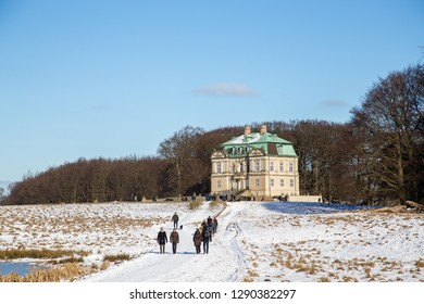 Klampenborg, Denmark - February 12, 2017: The hunting lodge and people walking in the snowy Deer Park