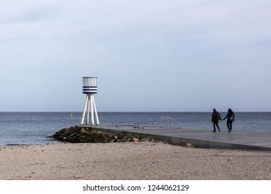 Klampenborg, Denmark - March 25, 2017: A couple walking towards a lifeguard tower at Bellevue Beach