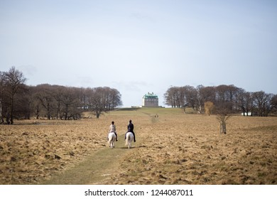 Klampenborg, Denmark - March 25, 2017:  Two horse riders in front of the small castle inside the Deer Park Dyrehaven