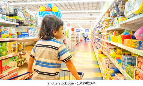 Klang Malaysia, 10 March 2018. Adorable boy grimacing sitting in shopping cart in toys department in supermarket