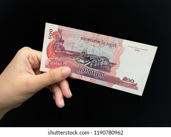 Klang , Malaysia - 11 September 2018 : Concept image of hand hold a Combodia money with black background.Business/Education concept.
