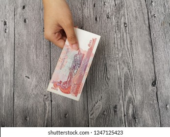 Klang , Malaysia - 11 September 2018 : Concept image of hand hold a 500 Combodia riel money on wooden background.Business/Education concept.