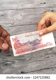 Klang , Malaysia - 11 September 2018 : Concept image of hand giving a 500 Combodia riel money with black background.Business/Education concept.