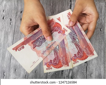 Klang , Malaysia - 11 September 2018 : Concept image of hand hold a 500 Combodia riel money with black background.Business/Education concept.