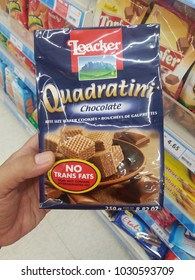 Klang , Malaysia - 15 February 2018 : Hand hold a packet of LOACKER Quadratini wafer cookies chocolate flavour at the supermarket.