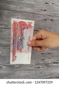 Klang , Malaysia - 28 November 2018 : Concept image of hand hold a 500 Combodia riel money on wooden background.Business/Education concept.