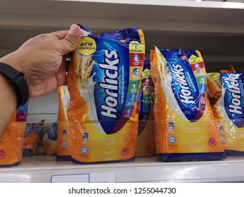 Klang, Malaysia - 4 December 2018 : Hand pickup a new design packed of Horlicks, a healthy malted milk drinks for sell in the supermarket.