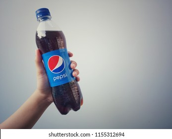 Klang, Malaysia - 7 August 2018 :Hand hold a bottle of Pepsi cola with vintage background.Pepsi is a carbonated soft drink that is produced and manufactured by PepsiCo.created and developed in 1893.